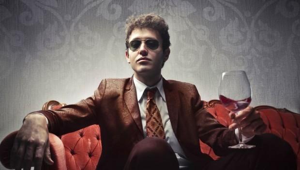 mężczyzna w ciemnych okularach z kieliszkiem wina w ręku.